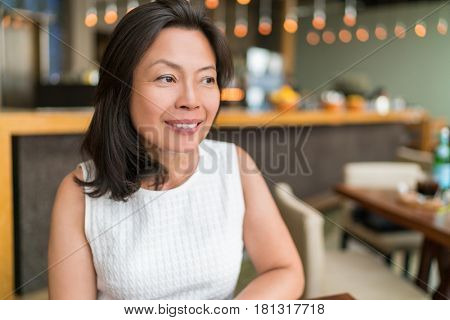 Happy healthy Asian middle-aged business woman relaxing inside restaurant. Beautiful mature Chinese business woman portrait in fancy restaurant. Beauty aging skin care.