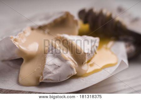 Brie cheese, slices, honey on parchment partial blur closeup horizontal