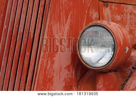 Weathered Grill of a Red Vintage Fire Truck with One Headlight