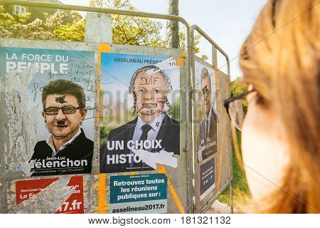 STRASBOURG FRANCE - APR 12 2017: Woman looking at official campaign posters of Jean-Luc MelenchonFrancois Asselineau political party leaders ones of the eleven candidates running in the 2017 French presidential election