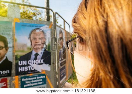 STRASBOURG FRANCE - APR 12 2017: POV of woman looking at official campaign posters of Francois Asselineau political party leaders ones of the eleven candidates running in the 2017 French presidential election