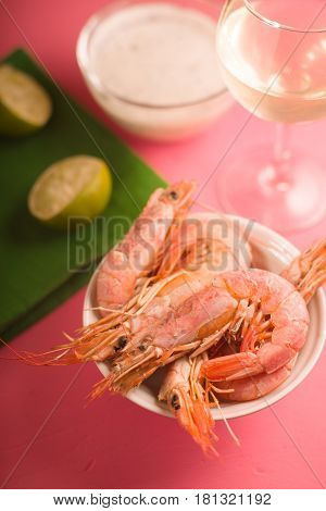 Shrimps in a ceramic bowl, a glass of white wine and a sauce partial blur vertical