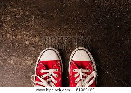 Red sneakers on a dark marble background. Footwear for outdoor activities. Object on a dark background. Transparent object. Conceptual object. The objects are on the table. The object is on marble. The object lies on the surface