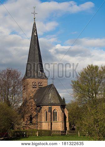 St. Antonius church in Hanselaer Kalkar Germany with dark clouds in the background