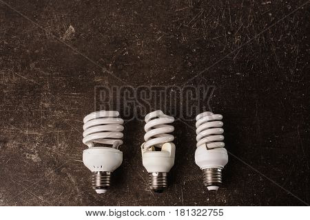 Fluorescent light bulb on a dark marble background. To save energy. Eco concept. Object on a dark background. Transparent object. Conceptual object. The objects are on the table. Object on marble. Object on a dark background. Transparent object. Conceptua