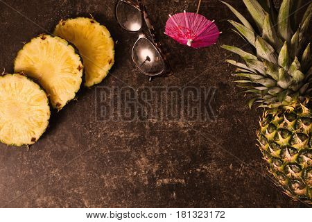 Ripe pineapple and cocktail umbrellas leopard sunglasses on dark table with a marble texture with scratches. Cut fruit. Healthy eating. Going on a journey to the south. Flat lay top view. Copyspace