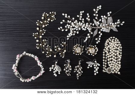 Jewelery for hair and white earrings made of beads on a dark background. Women's jewelry. Jewelery concept. Jewelery on dark table