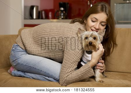 Pretty young adult attractive brunette woman with her Yorkshire terrier puppy lying on sofa