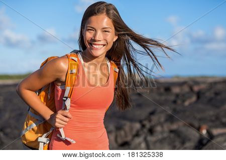 Happy backpacking girl tourist on travel adventure. Young hiking Asian backpacker woman hiker walking on lava rocks in Hawaii near Kilauea volcano. Active lifestyle.