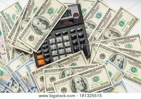 Love money account. Calculator nestled among the dollar bills.