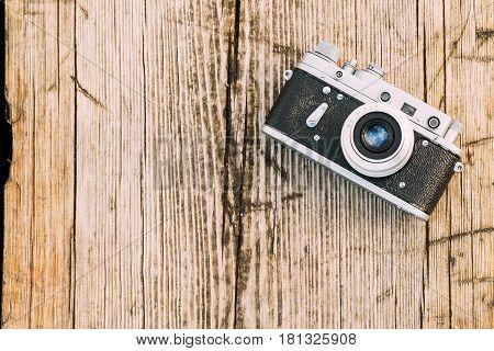 35mm Vintage Old Retro Small-Format Rangefinder Camera On Old Wooden Boards Desk Surface.