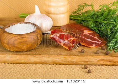 simple farm bacon stranded on a fork with pepper on wooden plate
