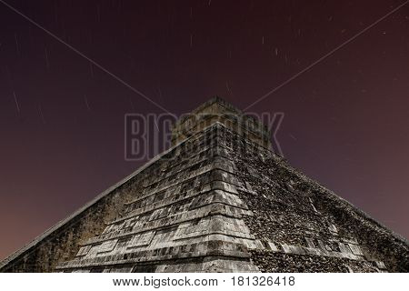 Ancient Mayan pyramid of Kukulcan at nigth with star trails at Chichen Itza, Yucatan, Mexico.