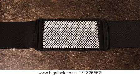 Belt for weight loss on a dark marble background. Relieve weight
