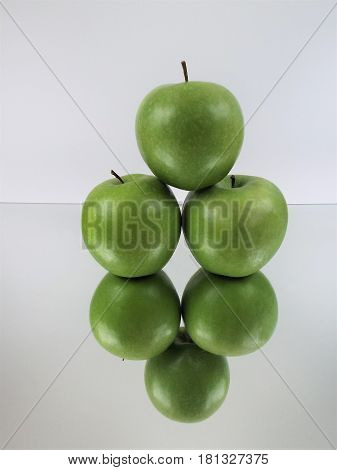 Reflection of three green apples on mirror.