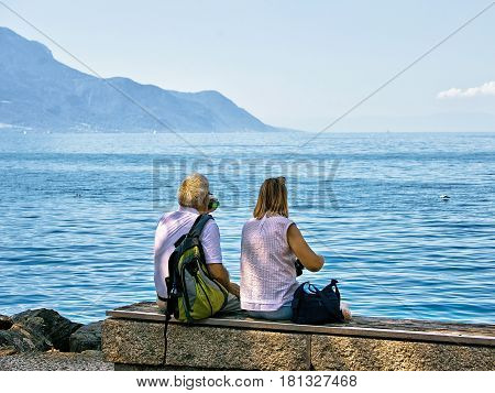Montreux, Switzerland - August 30, 2016: Couple sitting on the bench at the embankment of Geneva Lake in Montreux Vaud canton Switzerland