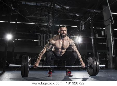 Muscular  Shirtless Man Preparing To  Deadlift A Barbell Over Hi