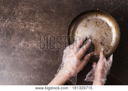 Wash the frying pan on a dark marble background. Hygiene. Wash dishes with gloves. Wash pan concept