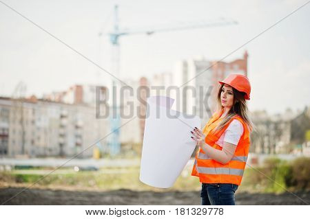 Engineer Builder Woman In Uniform Waistcoat And Orange Protective Helmet Hold Business Paper Against