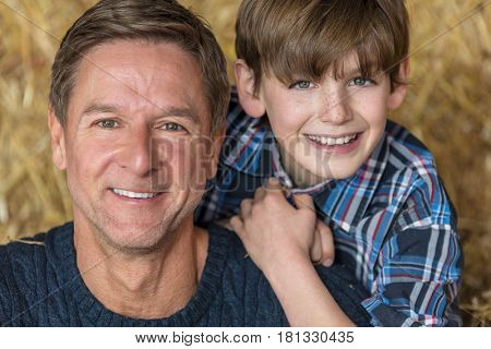 Portrait shot of an attractive, successful and happy middle aged man male wearing a blue sweater sitting on hay bales with his male child boy son in a barn or stables