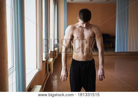 Young smart man with tight athletic body doing morning workout in the fitness training room. Sport concept. Fitness trainer.