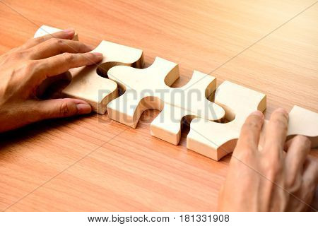 hand holding wood jigsaw piece texture pattern on wood table background