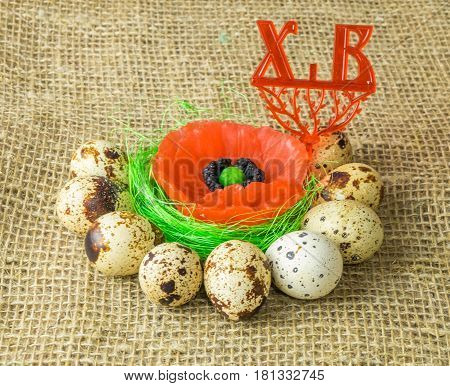 poppy lies on the filler sisal green light green color surrounded by quail eggs on a wooden table covered with burlap