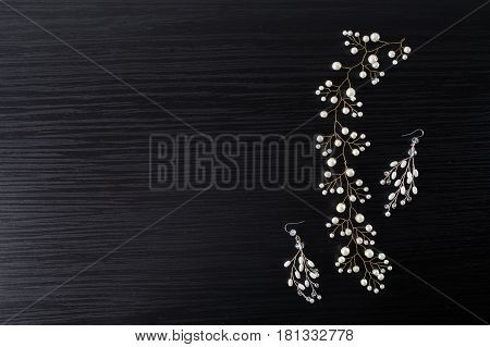 Jewelery for hair and white earrings made of beads on a dark background. Women's jewelry. Jewelery concept. Jewelery on table