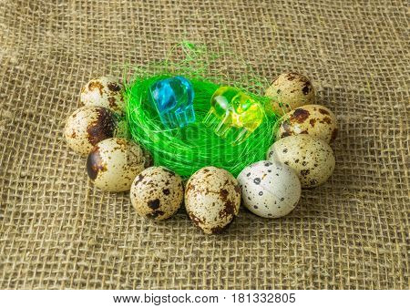 two elephant yellow and blue lies on the filler sisal green light green color surrounded by quail eggs on a wooden table covered with burlap