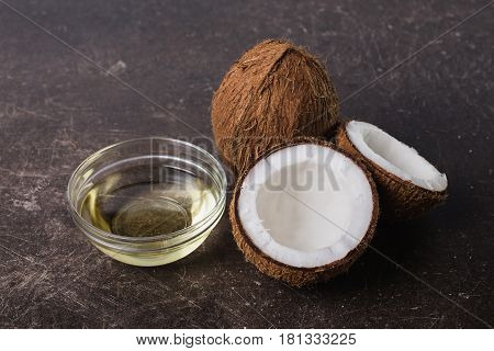 Coconut and coconut oil on a dark marble background. Exotic large walnut. Personal care. Spa treatments. Coconut concept. Coconut milk. Coconut on table