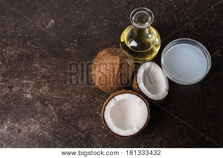 Coconut and coconut milk on a dark marble background. Exotic large walnut. Personal care. Spa treatments. Coconut concept. Coconut milk. Coconut on table