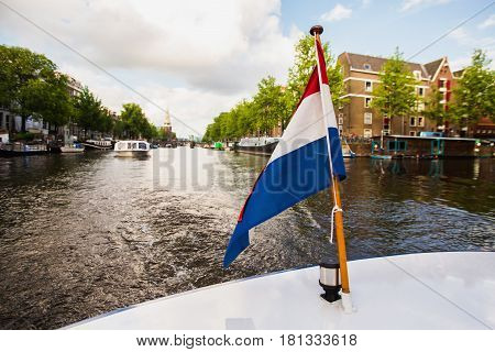 Dutch flag. Spring sunny Amsterdam. The bright clear blue sky with white clouds. Boat trip on the canals of Amsterdam. The bridge over the water. Travel to Europe