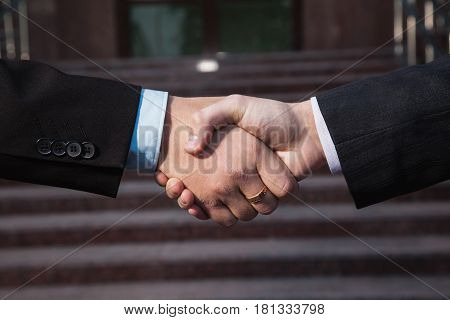 Business agreement. Handshake on background Bank. Shake hand with each other. Friendship partners. Shake your hand. Hand close-up. The man is pulling his hand. Men's hand
