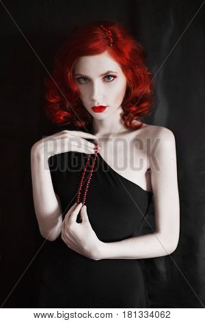 A woman with red curly hair in a black skin-tight dress on a black background. Red-haired girl with pale skin a thin waist blue eyes a bright unusual appearance red lips. Retro makeup