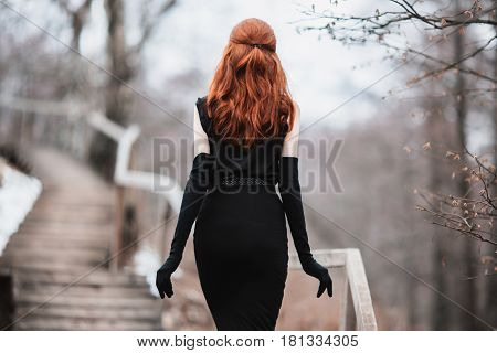 Striking thin girl with long red hair in black clothes. Thin woman in black dress and long black gloves posing on a background of winter autumn nature. Female street fashion style. Beautiful elegant thin model