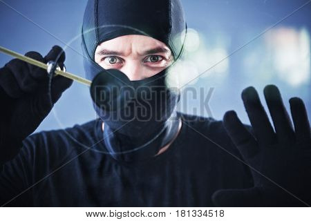 burglar in action with circular glass cutter