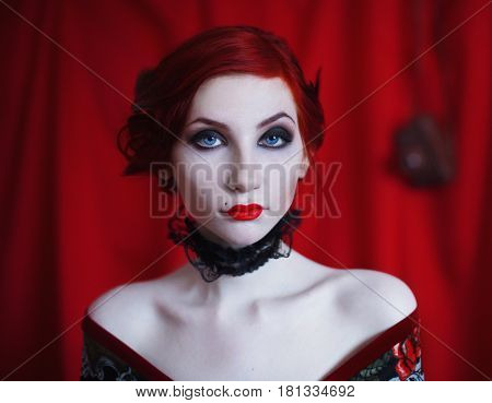 A woman with red curly hair in a black dress and retro makeup on a red background. Red-haired girl with pale skin blue eyes a bright unusual appearance red lips and a fatal face. Noir woman