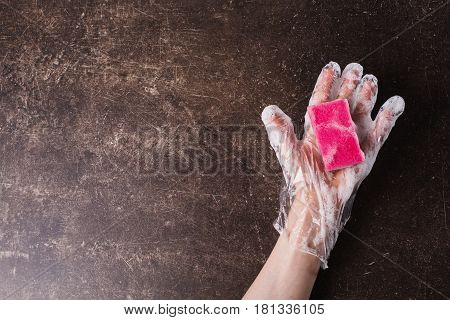 Hand in plastic hygienic gloves with a sponge on a dark marble background. Tidy up the house. Wash the dishes