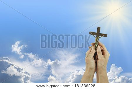 Praise to Our Lord - Female hands gently holding a Crucifix of Jesus Christ up towards a shining sun in a blue sky background with copy space on the left
