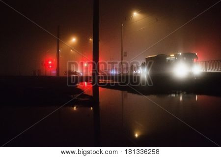 Dark city at night in dense fog. Thick smog on a dark street. Beautiful mixed light from the street lamps. Dark silhouettes of people and trees. Pillars at road. Dark night