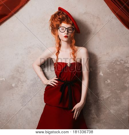 A retro woman with red hair in a red dress. Red-haired  retro girl with pale skin and blue eyes with a bright unusual appearance with a retro beret on her head on a gray background. French courtesan. Retro model
