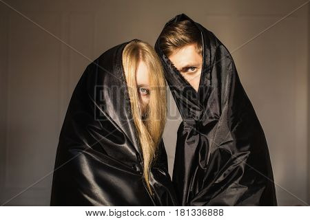 The mystical girl with long blonde hair and a man in black cloth on faces. Conceptual mystical photography. Piercing look. Anonymity. Portrait mystical photography.