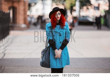 Woman style with red curly hair in blue coat and black round glasses on background of big city. Red-haired style girl with pale skin and bright appearance with black hat on head and bag on shoulder. Street style