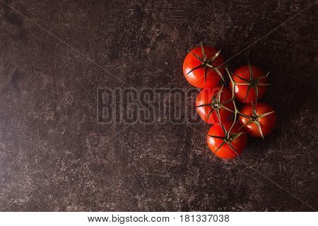 Red tomatoes lie on a dark marble table. Space for text and design. Flat lay ingredient copyspace. Ingredient for salad. Ingredients for the dish. Ingredient for a healthy diet.