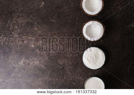 Coconut cream coconut milk and oil on a dark marble background. Exotic large walnut. Personal care. Spa treatments. Coconut cream concept. Spa cream