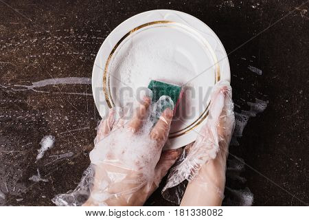 White dish detergent and sponge for dishes on a dark marble background. Hygiene. Wash dishes with gloves