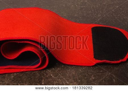 Belt for weight loss on a dark marble background. Relieve weight with belt. Red belt concept