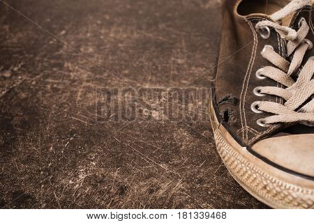 Old black sneakers on a dark marble background. Footwear for outdoor activities. Footwear concept. Footwear for sport