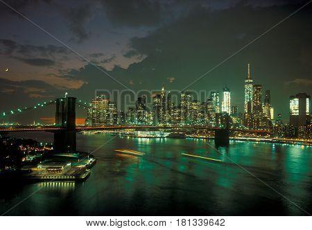 Manhattan skyline with Brooklyn Bridge at sunset.
