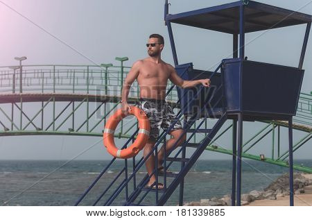 Safety rescue vacation. bearded lifeguard muscular man with muscle torso with orange ring buoy for life saving on duty on tower overlooking sea ocean beach sunny summer day on blue sky background